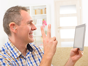 Deaf man talking using sign language on a tablet
