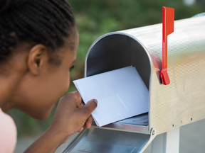 Girl putting letter in mailbox